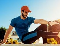 蹲着坐踢腿运动的蓝衣男子摄影图片