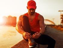 黄昏海边系鞋带的运动男子摄影图片