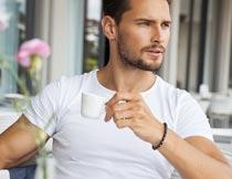 坐着拿咖啡杯的欧美帅哥摄影图片