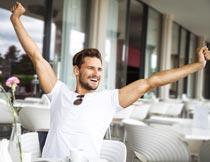 室外咖啡厅伸懒腰的型男摄影图片