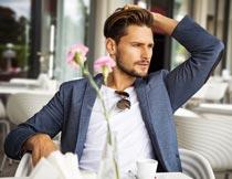 坐室外咖啡厅椅子上的型男摄影图片