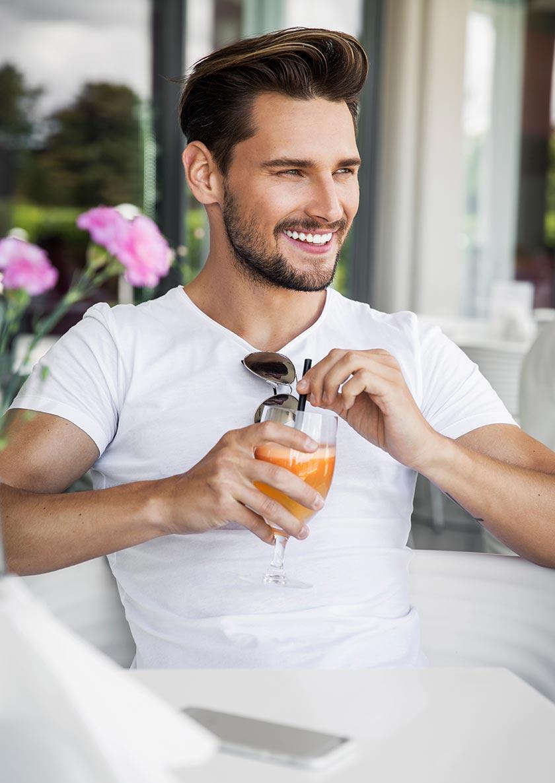 坐着开心喝果汁的欧美帅哥摄影图片