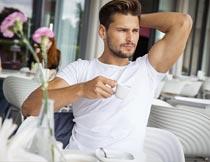 坐椅子上拿着咖啡杯的帅哥摄影图片