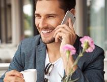 喝着咖啡开心打电话的帅哥摄影图片