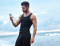 海边沙滩上看着水瓶的帅哥摄影图片