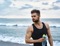 大海边拿着水瓶的肌肉型男摄影图片