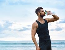 蓝天下海边喝水的肌肉猛男摄影图片