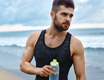 海边沙滩上拿水瓶的型男摄影图片