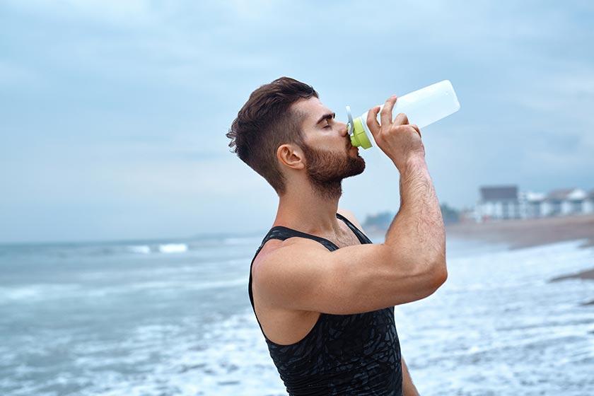 海边沙滩上喝水的帅哥侧面摄影图片