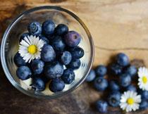 玻璃碗里的蓝莓与一朵鲜花高清图片