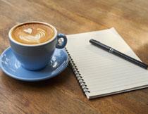 拉花咖啡与纸笔物品摄影高清图片
