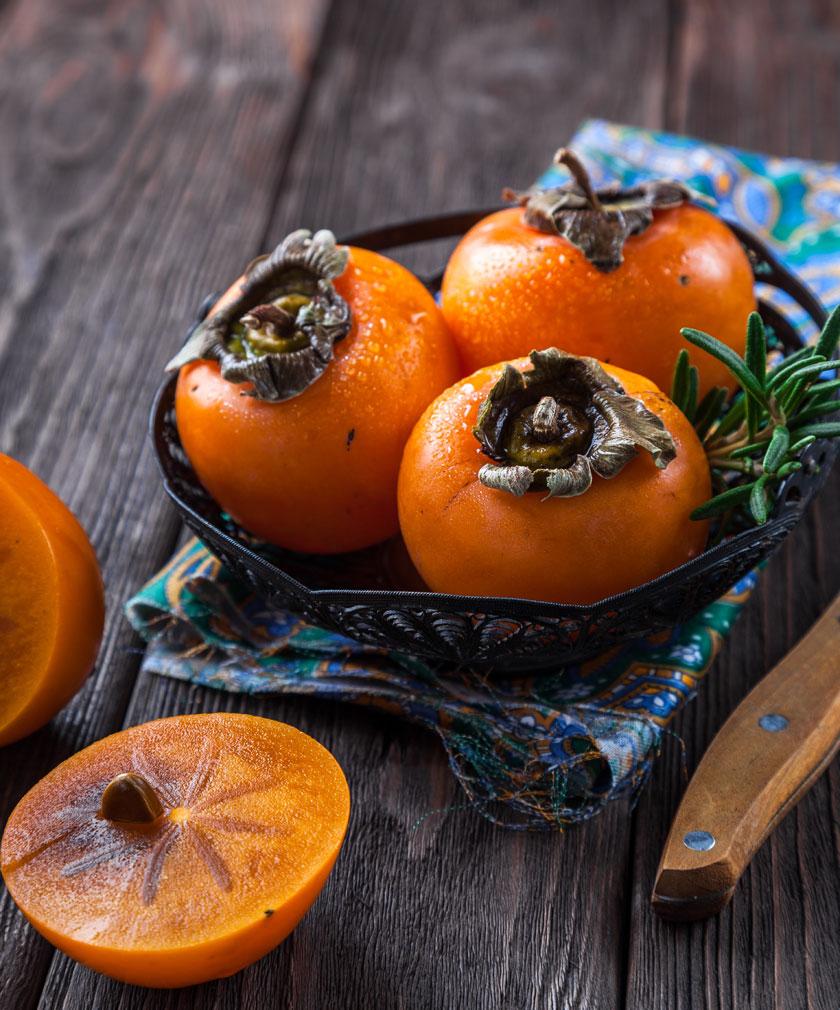 装盘摆放的成熟柿子摄影高清图片