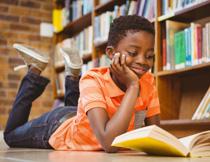 趴地板上看书的小男孩高清图片