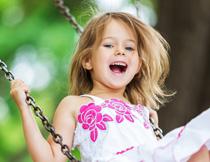 在玩荡秋千的开心小女孩高清图片