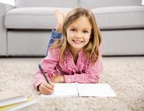 趴地摊上写字的小女孩高清图片