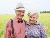 在油菜花田地里的夫妇高清图片