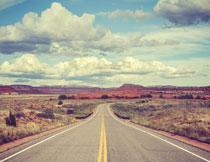 白云与公路两旁的草丛摄影图片