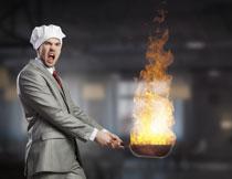 手掂着着火炒锅的男人创意图片