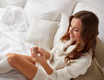 躺在床上玩手机的美女高清图片