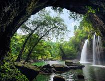 洞外瀑布与茂密的树林摄影图片