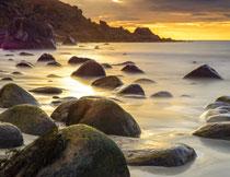 晚霞与露出水面的礁石高清图片