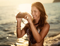 海边拿相机拍照的美女高清图片