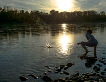 在河边打水漂的小男孩高清图片