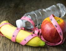 缠着软尺的香蕉与苹果高清图片