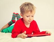 趴着在玩电脑的小男孩高清图片