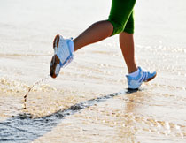 沙滩上跑步的人物摄影高清图片