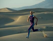 在沙漠中跑步的美女高清图片