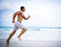 沙滩上跑步的赤膊男子高清图片