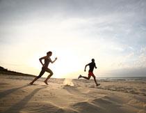 飞奔沙滩上的跑步男女高清图片
