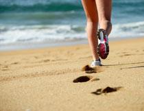 沙滩上跑步的人物局部摄影图片