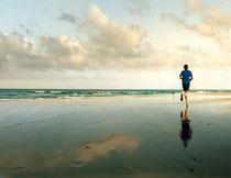 从沙滩上跑过去的男子高清图片