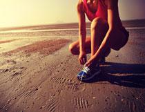 蹲下系鞋带的跑步人物高清图片