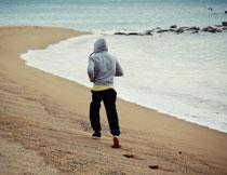 在海边跑步的男子摄影高清图片