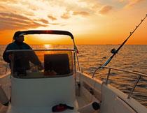 夕阳余晖下的钓鱼船只高清图片