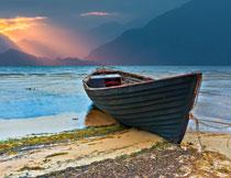 被拉上岸上的生锈小船高清图片
