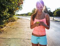 中途停下看手机的跑步美女图片