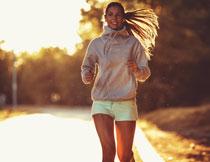 公路上慢跑的美女逆光摄影图片