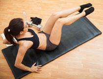 半仰卧双腿悬空的运动美女图片