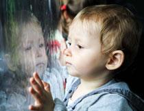 趴在玻璃上看着窗外的男孩图片