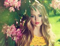 鲜花树枝下的金发美女高清图片