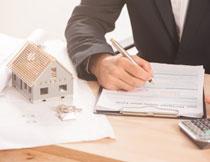 房屋模型与填写表格的人物图片