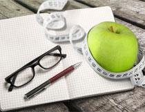 记事本上的眼镜与苹果高清图片