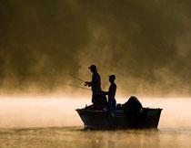 乘船在钓鱼的人物剪影高清图片