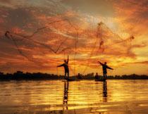 暮色之下撒网的捕鱼人高清图片