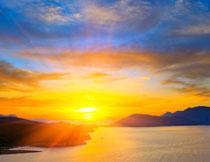 耀眼阳光下的山峦大海高清图片