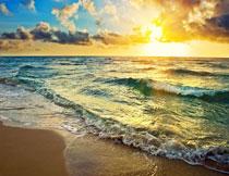 晨曦中涌向沙滩的潮水风光图片